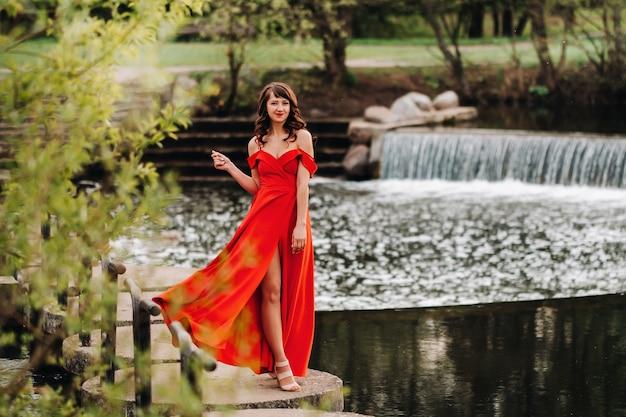 Ragazza in un lungo abito rosso vicino al lago nel parco al tramonto.