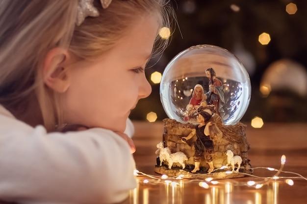 Ragazza che guarda una palla di vetro con una scena della nascita di gesù cristo in una palla di vetro su un albero di natale