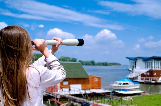 Ragazza che guarda il villaggio galleggiante delle barche e della casa del fiume con il telescopio binoculare. cercando l'estate. copi lo spazio