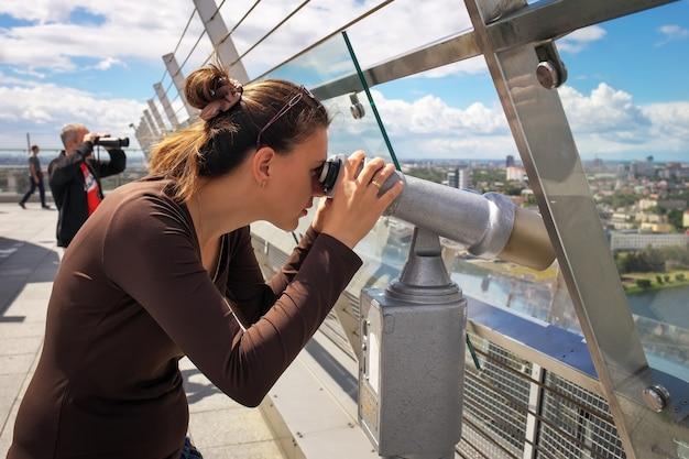 Ragazza che guarda attraverso un telescopio sul tetto di un edificio alto.
