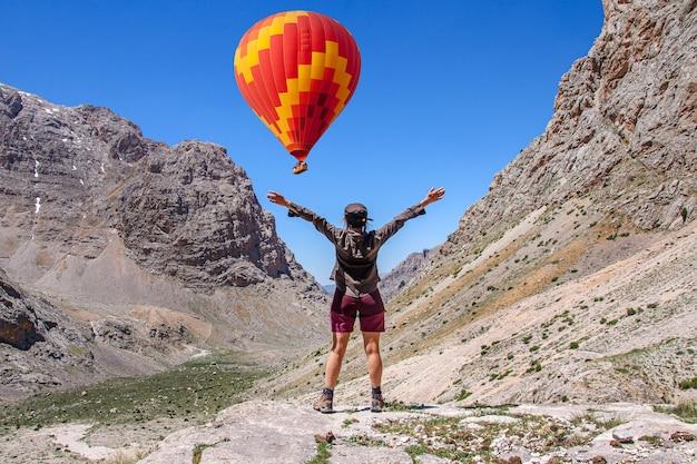 Una ragazza guarda una brillante mongolfiera in una bellissima valle della turchia