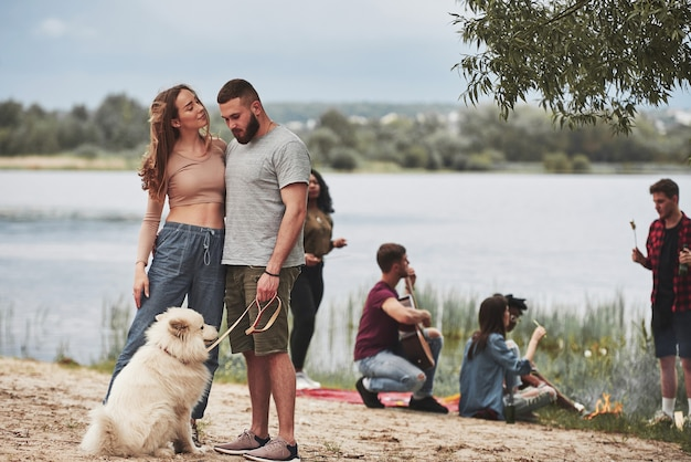 La ragazza guarda il suo uomo con amore. un gruppo di persone fa un picnic sulla spiaggia. gli amici si divertono durante il fine settimana.