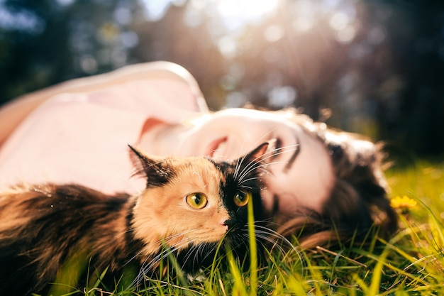 Ragazza che si trova sull'erba con il gatto. concetto di clima caldo primaverile o estivo.