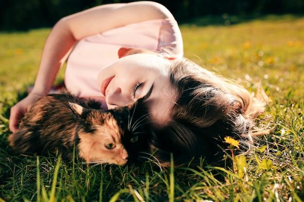 Ragazza che si trova sull'erba con il gatto. concetto di clima caldo primaverile o estivo. Foto Premium