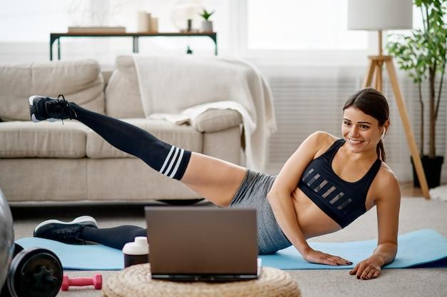 Ragazza sdraiata al laptop, formazione in linea in forma. persona di sesso femminile in abbigliamento sportivo, allenamento sportivo internet, interno della stanza