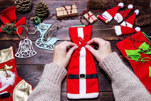 La ragazza fa i regali di natale su un tavolo di legno scuro.