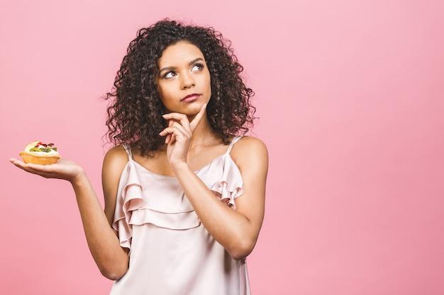 La ragazza prende la decisione. la ragazza afro americana non mangia la torta. concezione per perdere peso. isolato su sfondo rosa.