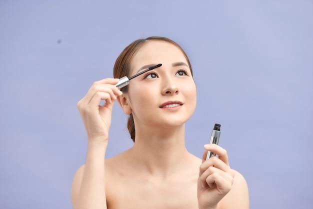 La ragazza fa il trucco. la bella donna applica il mascara sulle ciglia con il pennello cosmetico