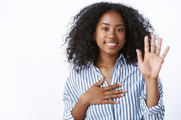 La ragazza fa una promessa. ritratto amichevole dall'aspetto sincero carino donna afro-americana che dice la verità alza una mano metti il braccio cuore impegnando, dando giuramento sorridente giurare, in piedi muro bianco