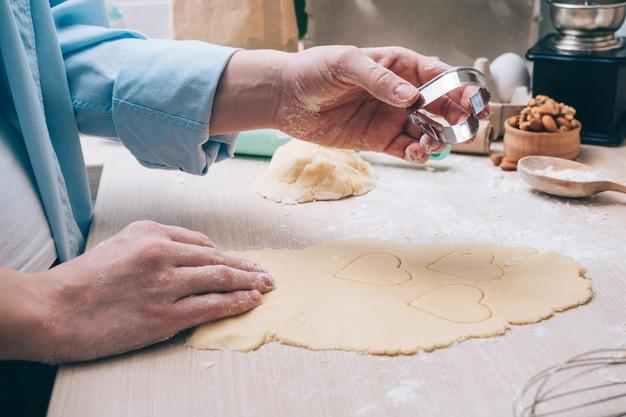 Ragazza che fa i biscotti a forma di cuore in cucina, primo piano. sorpresa per i tuoi cari a san valentino, festa della mamma o festa del papà. sfondo culinario festivo, con amore.
