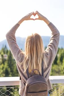 Ragazza che fa una forma di cuore con il paesaggio di montagna sullo sfondo.