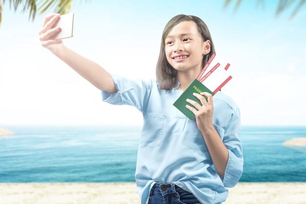 Ragazza che fa selfie tenendo biglietto e passaporto sulla spiaggia con uno sfondo di cielo blu