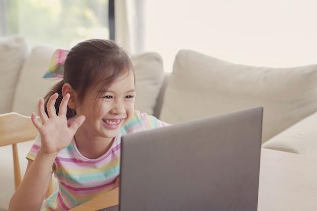 Ragazza che fa videochiamate con il computer portatile a casa, homeschooling, concetto di apprendimento a distanza