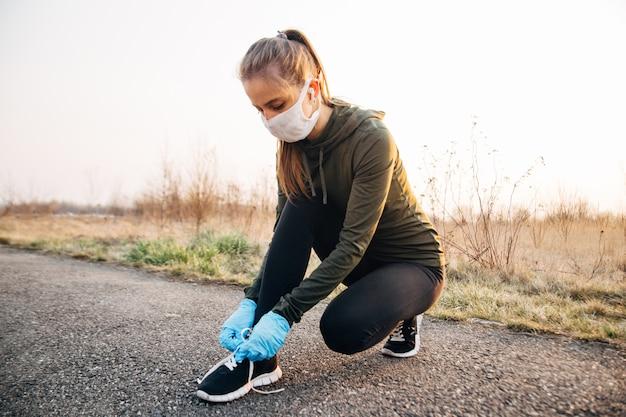 Ragazza in maschera e guanti blu durante la quarantena uscì per correre