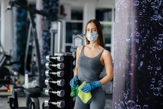 La ragazza con la maschera che disinfetta l'attrezzatura da palestra durante una pandemia