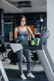 La ragazza con la maschera che disinfetta l'attrezzatura da palestra durante una pandemia.