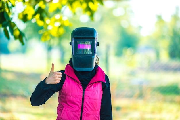La ragazza con una maschera da saldatore mostra un dito
