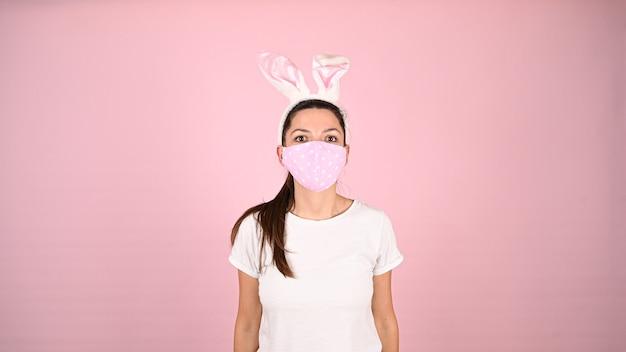 Ragazza in una maschera con orecchie da coniglio, su uno sfondo rosa. foto di alta qualità