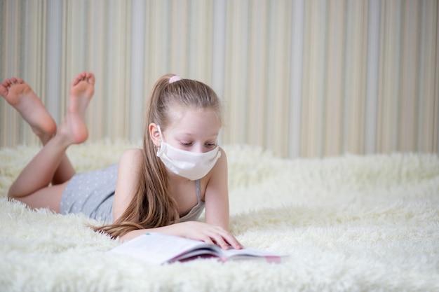 Una ragazza in una maschera con pelle chiara e capelli legge un libro sdraiato su un soffice copriletto leggero a casa