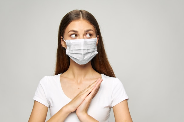 Maschera medica della ragazza sul viso, guarda lo stile di vita della maglietta bianca laterale