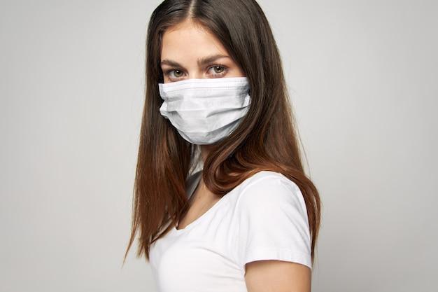 La ragazza in una mascherina medica sul suo viso guarda avanti la salute della maglietta bianca dei capelli lunghi