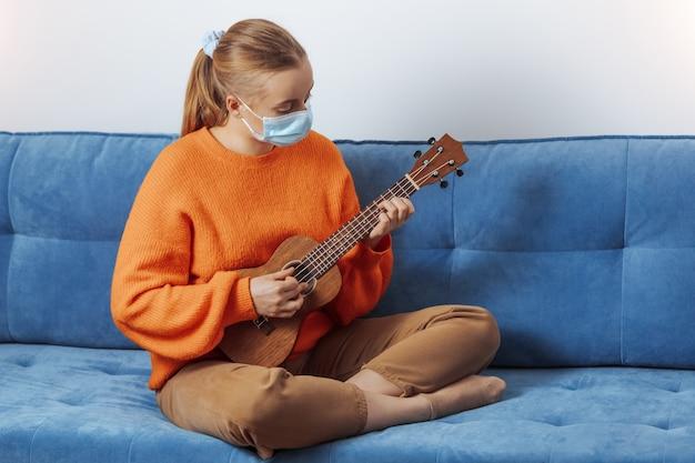 Una ragazza con una maschera medica impara a suonare l'ukulele mentre è seduta sul divano di casa