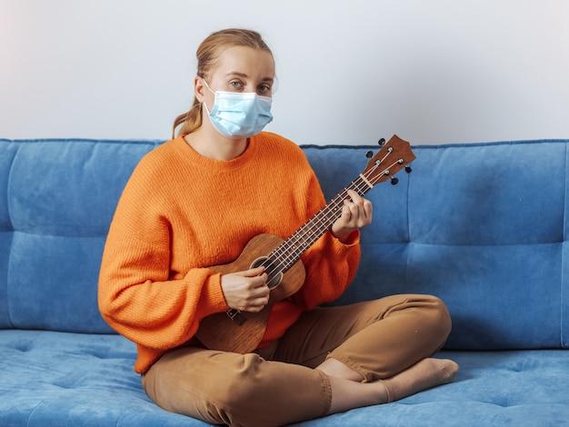 Una ragazza con una maschera medica suona l'ukulele