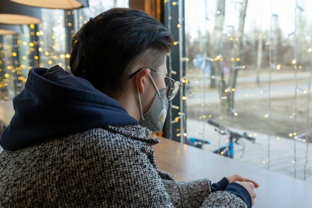 Una ragazza con una maschera medica si siede in un caffè e guarda tristemente fuori dalla finestra