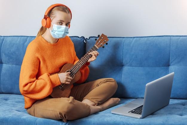 Una ragazza con una mascherina medica si siede sul divano di casa e impara a suonare l'ukulele a distanza