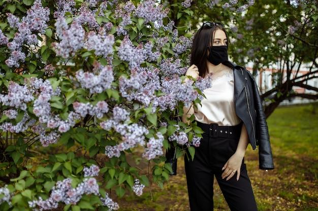 Ragazza in una maschera medica con lillà in fiore. maschera nera. protezione contro la protezione dal coronavirus. epidemia di coronavirus. l'aroma di un albero in giardino allergia primaverile