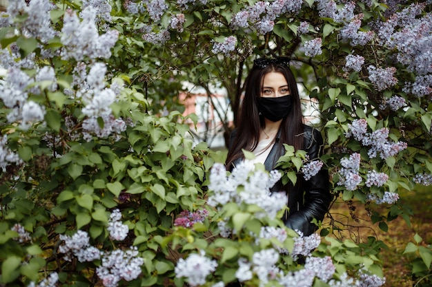 Ragazza in una maschera medica con fioritura lilla nel parco. maschera nera. protezione dal coronavirus. allergia primaverile