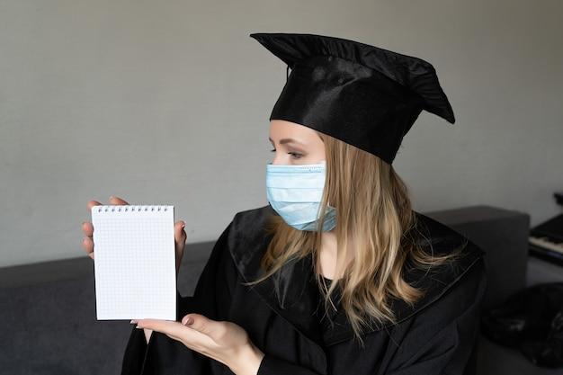 Ragazza in maschera medica con cappello da abito da laurea che tiene un piccolo taccuino su sfondo grigio