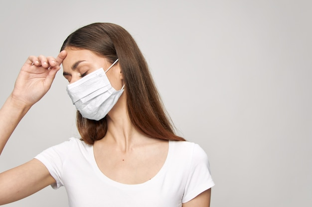 Ragazza nella mascherina medica con la mano vicino al fondo isolato della maglietta bianca degli occhi chiusi del fronte