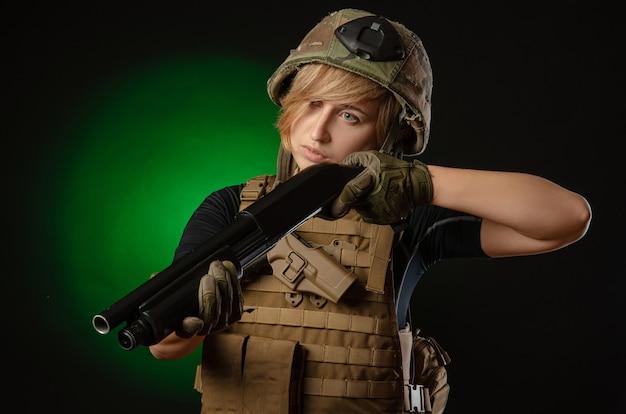 La ragazza in uniforme militare mira con un fucile da caccia