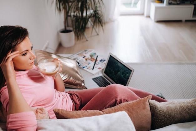 Una ragazza al mattino in pigiama a casa che lavora su un laptop bevendo caffè, una ragazza autoisolata a casa e che riposa sul divano e guarda un laptop.faccende domestiche