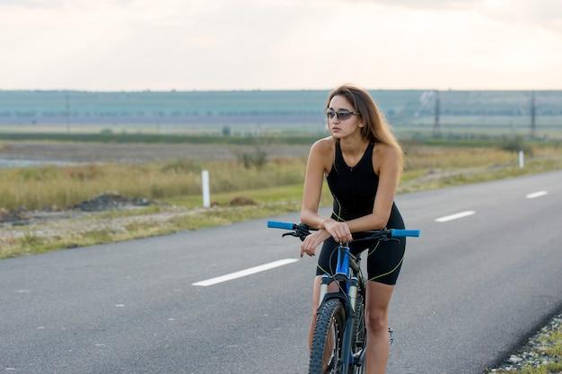 Ragazza su una mountain bike in fuoristrada bellissimo ritratto di una ragazza ciclista che guida una moderna bici in carbonio