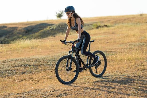 Ragazza su una mountain bike in fuoristrada bellissimo ritratto di un ciclista al tramonto