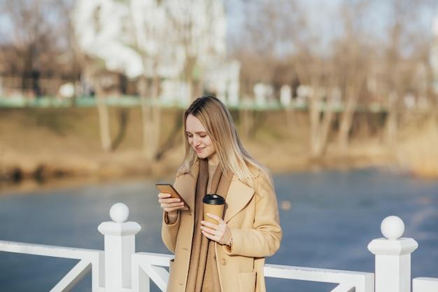 Ragazza sulla natura vicino al lago nella giornata di sole sta usando il telefono e beve caffè