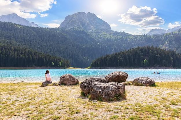 Una ragazza vicino al lago nero sul monte durmitor, montenegro.
