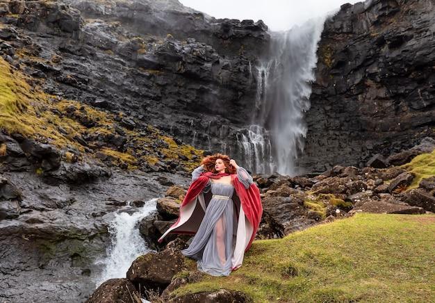 Una ragazza in abiti antiquati con un mantello rosso rimane vicino alla cascata di fossa, streymoy, isole faerøer