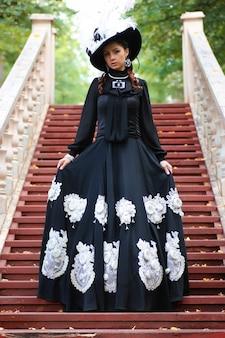 Ragazza in vecchio vestito retrò sulle scale all'aperto