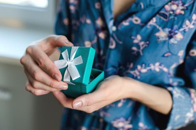 La ragazza ha aperto il coperchio della confezione regalo, blu, con un nastro bianco, vestiti blu