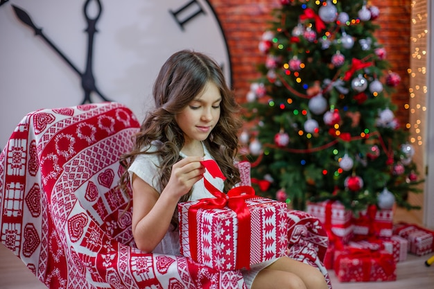 Una ragazza apre un regalo vicino all'albero di natale