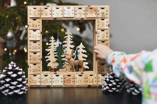 Una ragazza apre il calendario dell'avvento in legno con i regali