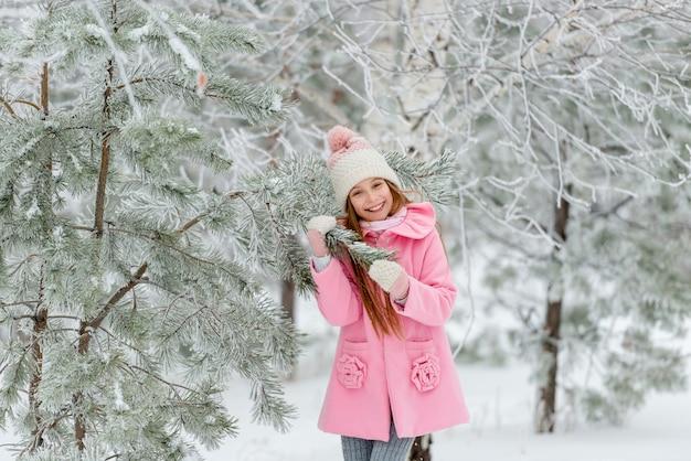 Ragazza fuori in inverno vicino all'albero di natale