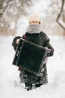 Ragazza in giacca calda oversize in piedi nella neve con la fisarmonica