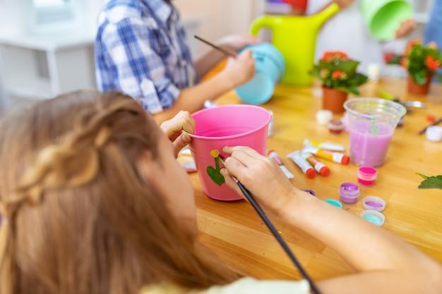 Pittura della ragazza. primo piano di una ragazza dai capelli scuri che dipinge con tempera su un secchio rosa per pianta
