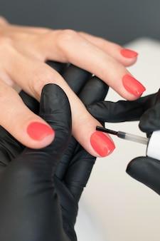Ragazza pittura unghie, manicure maestro al lavoro