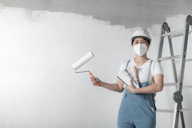La ragazza dipinge un muro bianco con un rullo