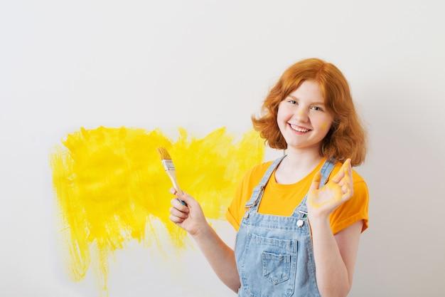 La ragazza dipinge il muro bianco in giallo